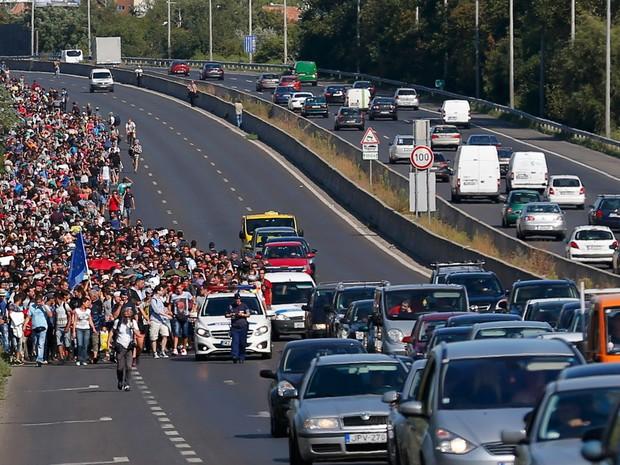 Migrantes marcham por uma estrada nos arredores de Budapeste, na Hungria, para a fronteira com a Áustria. Uma lei aprovada nesta sexta (4) pelo Parlamento da Hungria prevê penas de até três anos de prisão para o cruzamento ilegal de suas fronteiras (Foto:  Laszlo Balogh/Reuters)