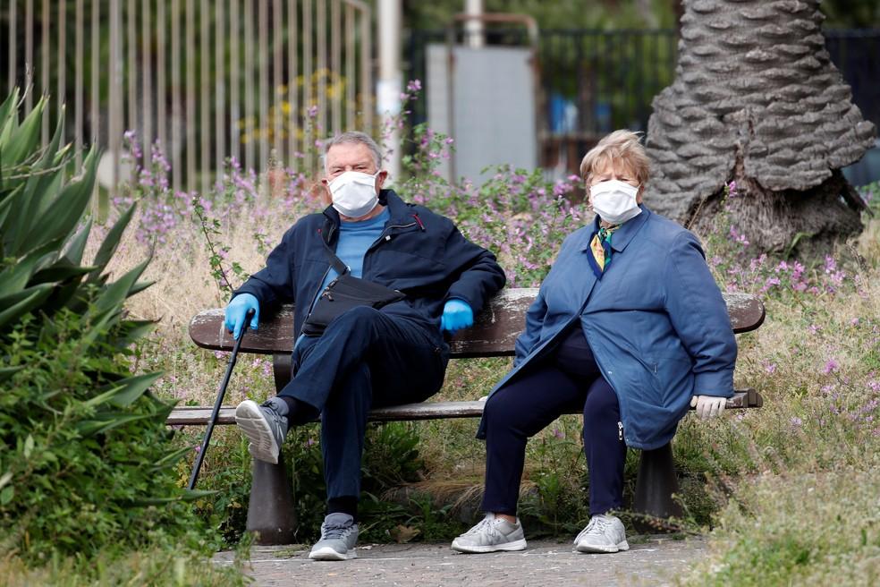 Casal sentado em banco usa máscara durante pandemia do coronavírus em Nápoles, Itália — Foto: Reuters/Ciro De Luca
