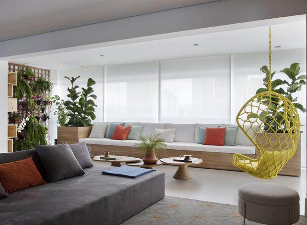 Um longo banco de madeira preenche a largura da primeira varanda. Cercado de plantas, o espaço é disputado nos momentos de descanso (Foto: Denilson Machado/MCA Estúdio/Divulgação)