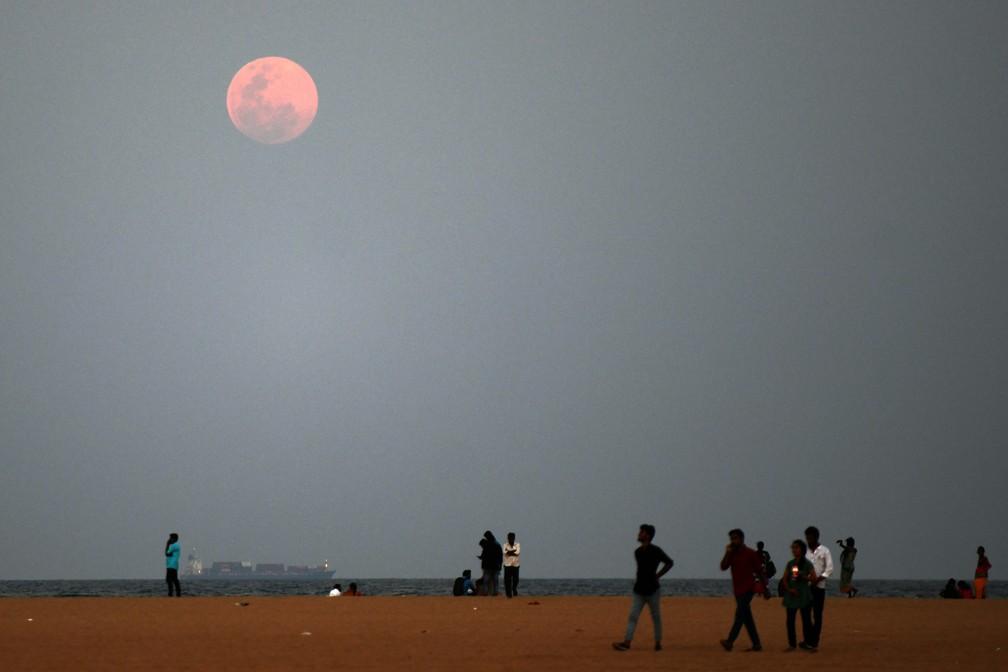 Moradores caminham na praia Marina, em Chennai, no sul da Índia — Foto: Arun Sankar/AFP