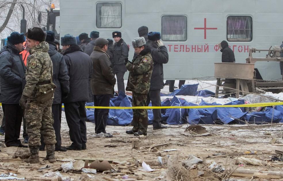 Membros da equipe de resgate se reúnem perto das vítimas da queda de um avião de carga turco no Quirguistão (Foto: Vladimir Pirogov/Reuters)