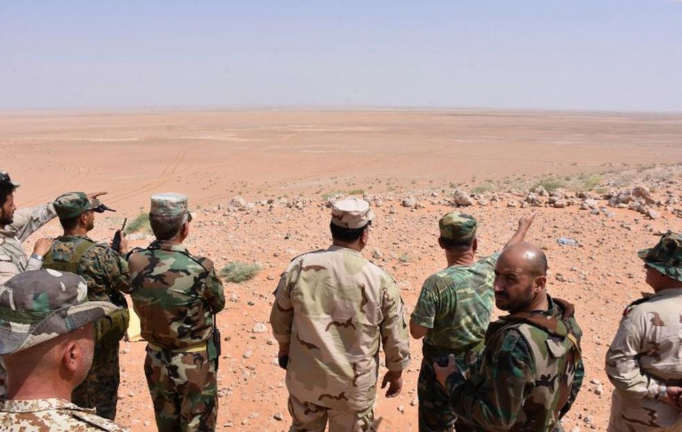 -  Forças do governo sírio olham o horizonte a partir de uma colina em Bir Qabaqib, a mais de 40 quilômetros a oeste de Deir Ezzor, em imagem de arquivo