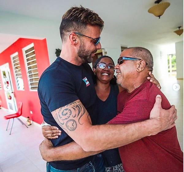 O músico Ricky Martin sendo abraçado por um casal que teve a casa reconstruída pela fundação administrada pelo artista (Foto: Instagram)