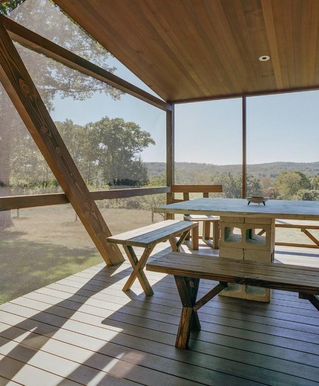 Móveis rústicos integram a varanda suspensa (Foto: Reprodução Domus )