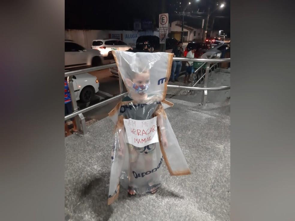 Gabriel, de 4 anos, aguardou a mãe na entrada de um hospital particular de Fortaleza vestido com uma roupa de plástico. — Foto: Arquivo pessoal