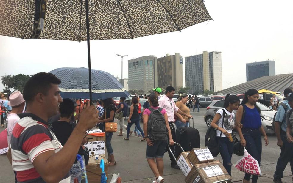 Ambulantes vendem sombrinhas e guarda-chuvas na rodoviária do Plano, no DF (Foto: Larissa Batista/G1)