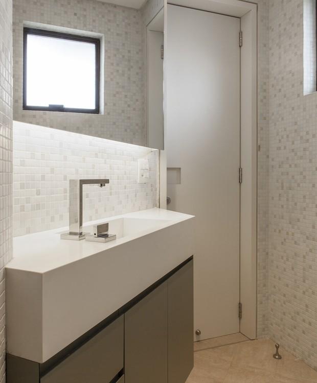 A planta triangular do banheiro desafiou os arquitetos. A cuba integrada à bancada ajudou a multiplicar o espaço e a criar um resultado elegante (Foto: Maíra Acayaba/Divulgação)
