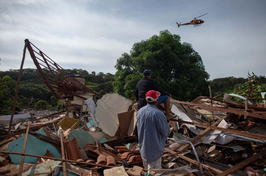 Moradores do Parque da Cachoeira, em Brumadinho (MG) observam passagem de helicóptero. — Foto: Mauro Pimentel/AFP