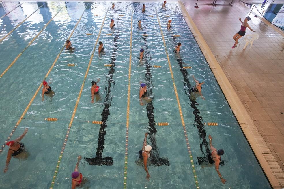 Uma aula de ginástica aquática é vista na piscina coberta de um centro esportivo em Roma, na Itália, durante sua reabertura após mais de dois meses de fechamento para impedir a propagação do coronavírus — Foto: Andrew Medichini/AP