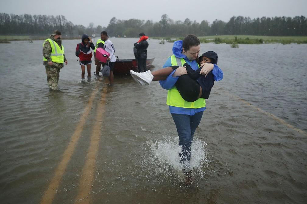 Crianças são resgatadas por voluntários nesta sexta-feira (14) em James City, uma das cidades atingidas pela tempestade do furacão Florence — Foto: Chip Somodevilla/ Getty Images North America/ AFP