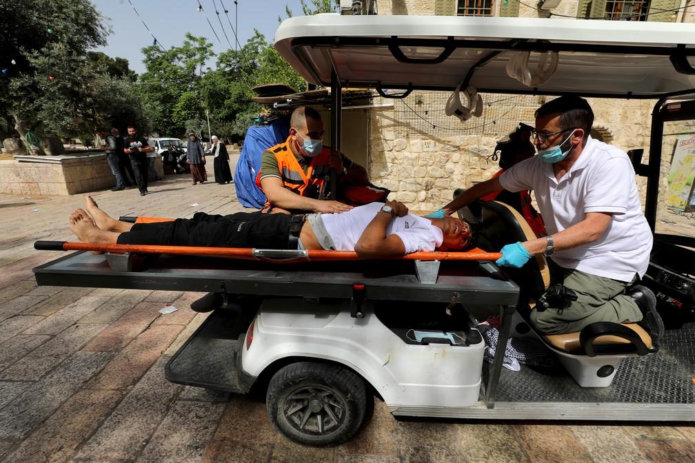 Palestino ferido é atendido durante confrontos com a polícia israelense no complexo que abriga a mesquita Al-Aqsa nesta segunda (10) — Foto: Ammar Awad/Reuters