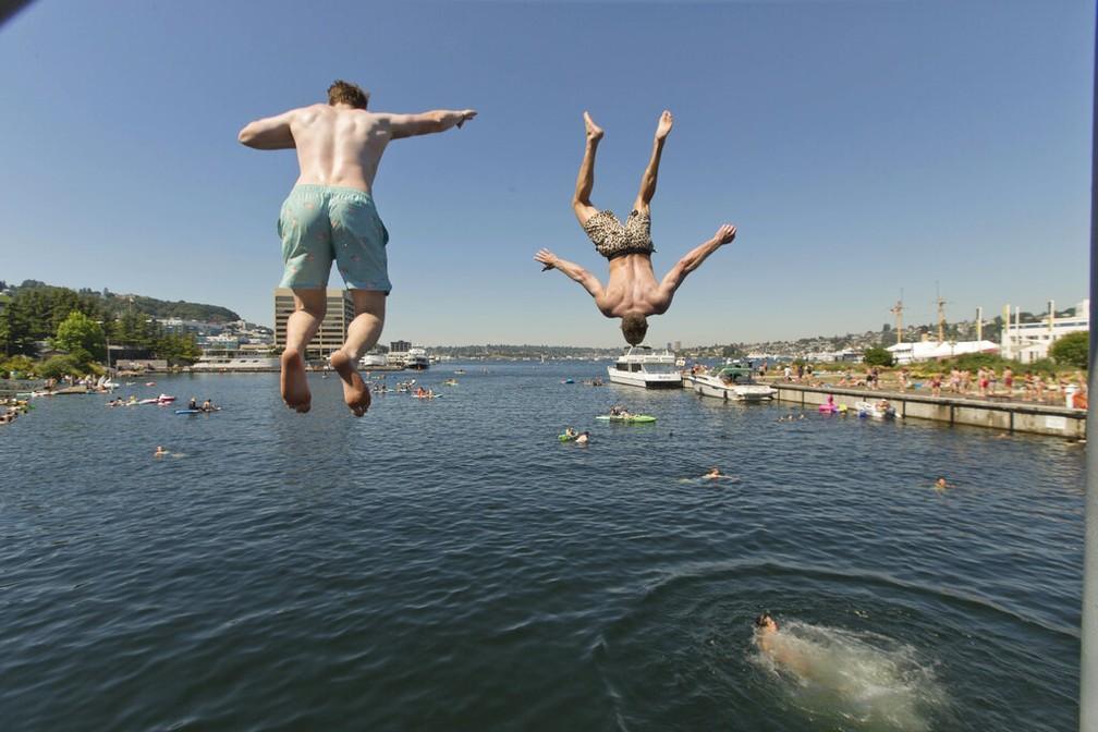 Pessoas saltam em lago em Seattle, nos EUA, neste domingo (27) — Foto: John Froschauer/AP Photo