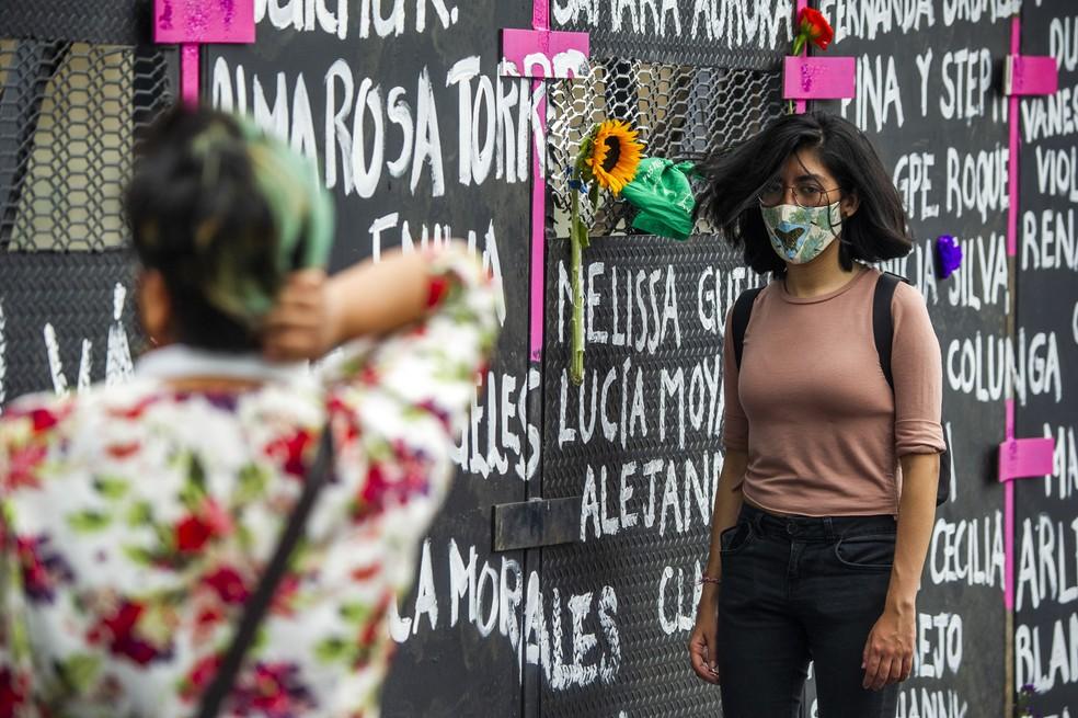 Jovem passa em frente a mural com nomes de vítimas de feminicídio no México erguido para o Dia Internacional da Mulher, em foto de 7 de março de 2021 — Foto: Claudio Cruz/AFP