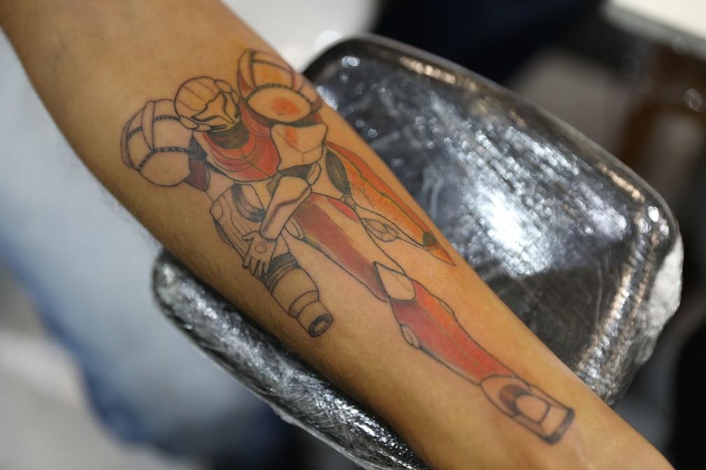 Celita Guimarães Porto tatua uma Samus, de 'Super Metroit', no assistente de laboratório Wellington Soares Gomes, de 28 anos, na CCXP 2018 — Foto: Fábio Tito/G1