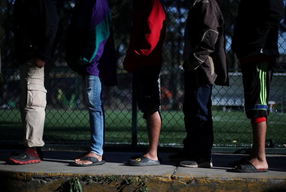 Migrantes fazem fila para receber alimentos em abrigo na Cidade do México — Foto: Hannah McKay/Reuters