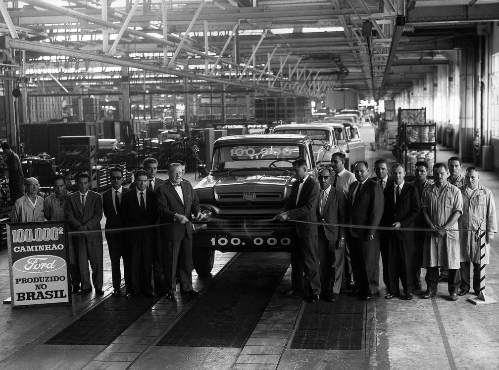 O gerente de manufaturas, J. Hutchens, acompanhado de sua equipe e empregados da montagem, participa do ato comemorativo da construção do caminhão de número 100.000 da marca Ford no Brasil, em fevereiro de 1964 — Foto: Estadão Conteúdo/Arquivo
