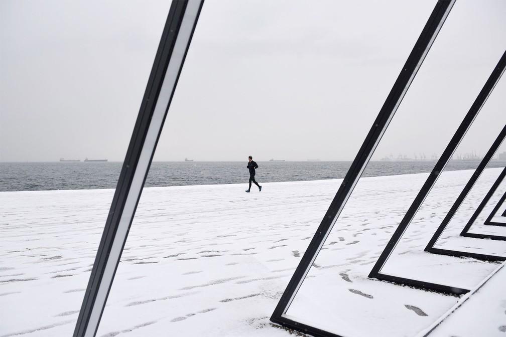 Homem pratica corrida em passeio coberto de neve à beira-mar em Tessalônica, na Grécia — Foto: Alexandros Avramidis/Reuters