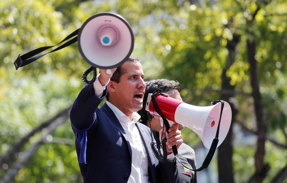 Juan Guaidó usa megafone para falar a multidão de cima de um carro em Caracas, após convocar o povo às ruas contra Maduro — Foto: Carlos Garcia Rawlins/Reuters