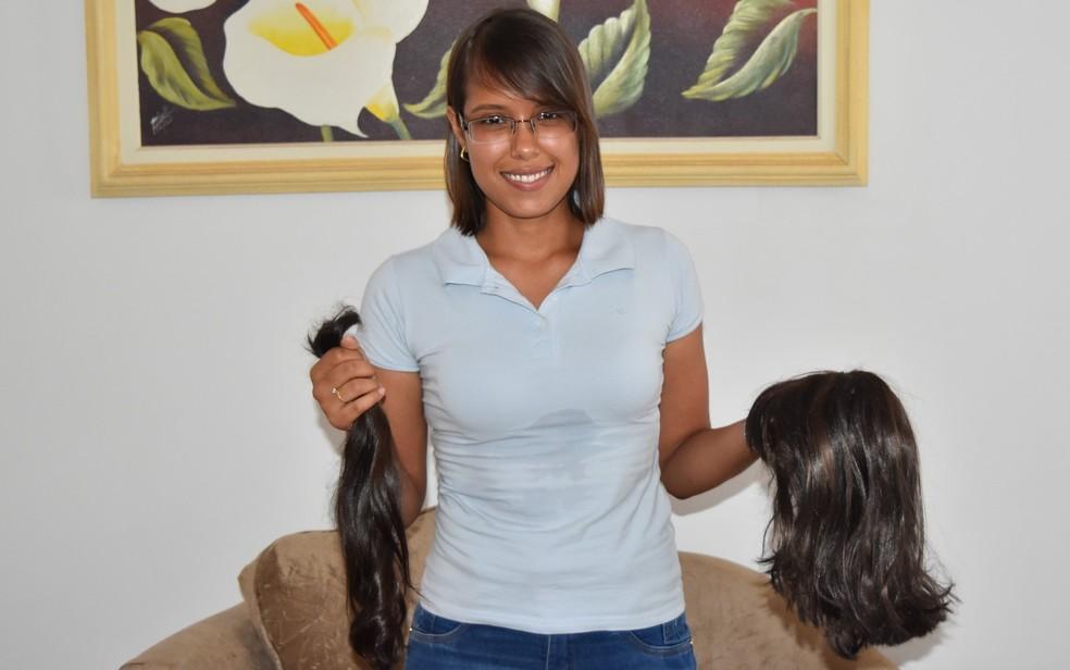 Alinne Silva Barbosa guarda o cabelo que cortou e a peruca que usava para ir à faculdade (Foto: Paula Resende/ G1)