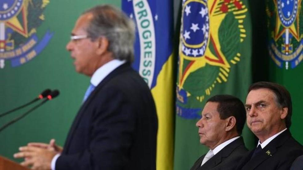 O ministro Paulo Guedes, com o presidente Jair Bolsonaro e o vice Hamilton Mourão — Foto: EVARISTO SA/AFP/Getty Images
