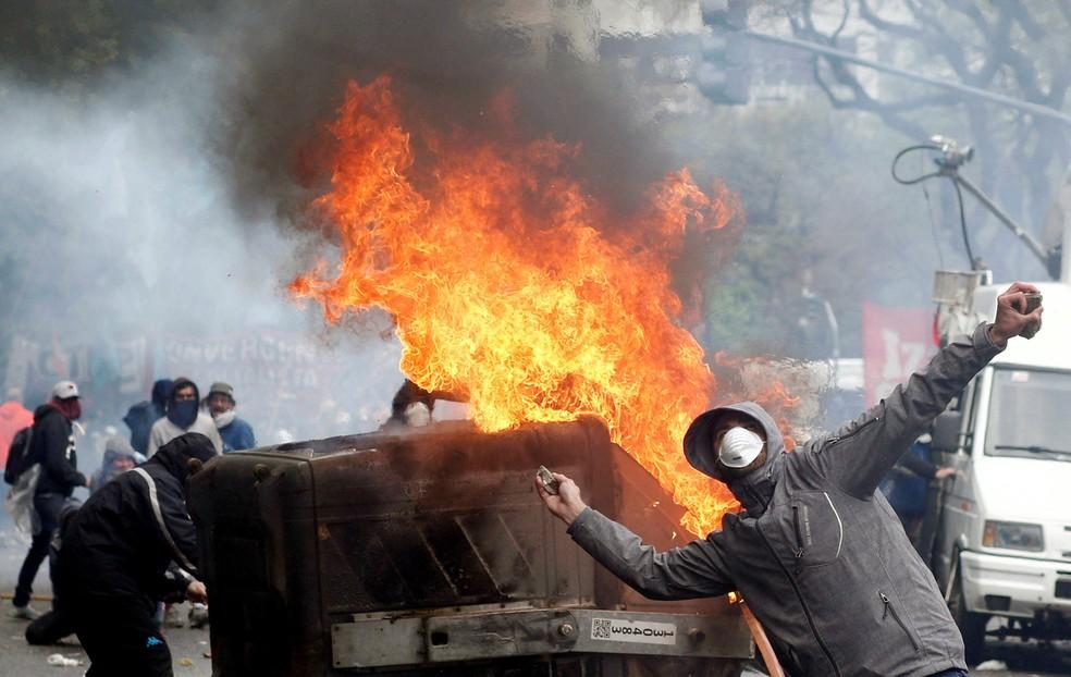 Manifestante joga pedra contra a polícia durante confrontos em frente ao Congresso da Argentina, em Buenos Aires. Deputados debatem a proposta de lei orçamentária para o próximo ano, que pretende implementar medidas de austeridade para o país, imerso em uma séria crise econômica — Foto: Martin Acosta/Reuters