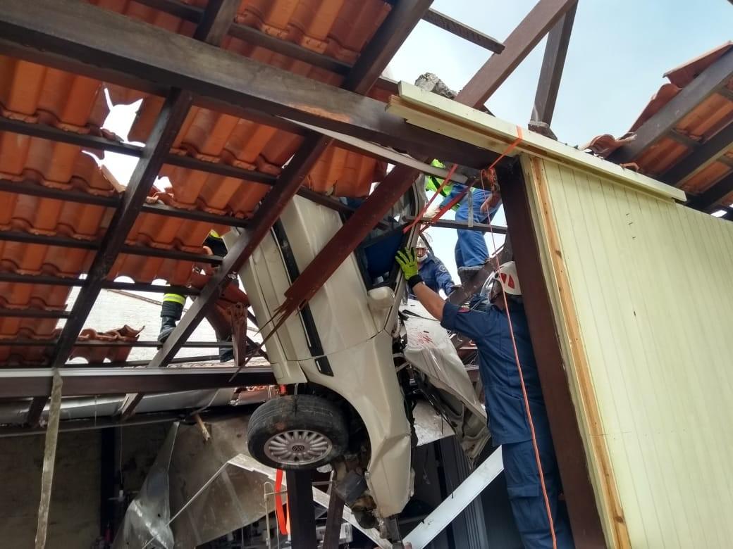 Carro fica pendurado em telhado após acidente em SC e motorista é resgatado pelos bombeiros
