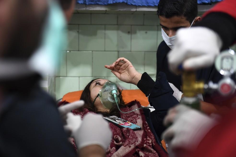 Mulher síria recebe tratamento em um hospital controlado pelo regime de Aleppo, neste sábado (24) — Foto: GEORGE OURFALIAN / AFP