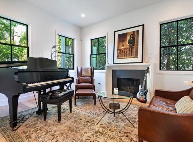 A sala ao lado do hall de entrada conta com piano, lareira e guitarra (Foto: Variety/ Reprodução)