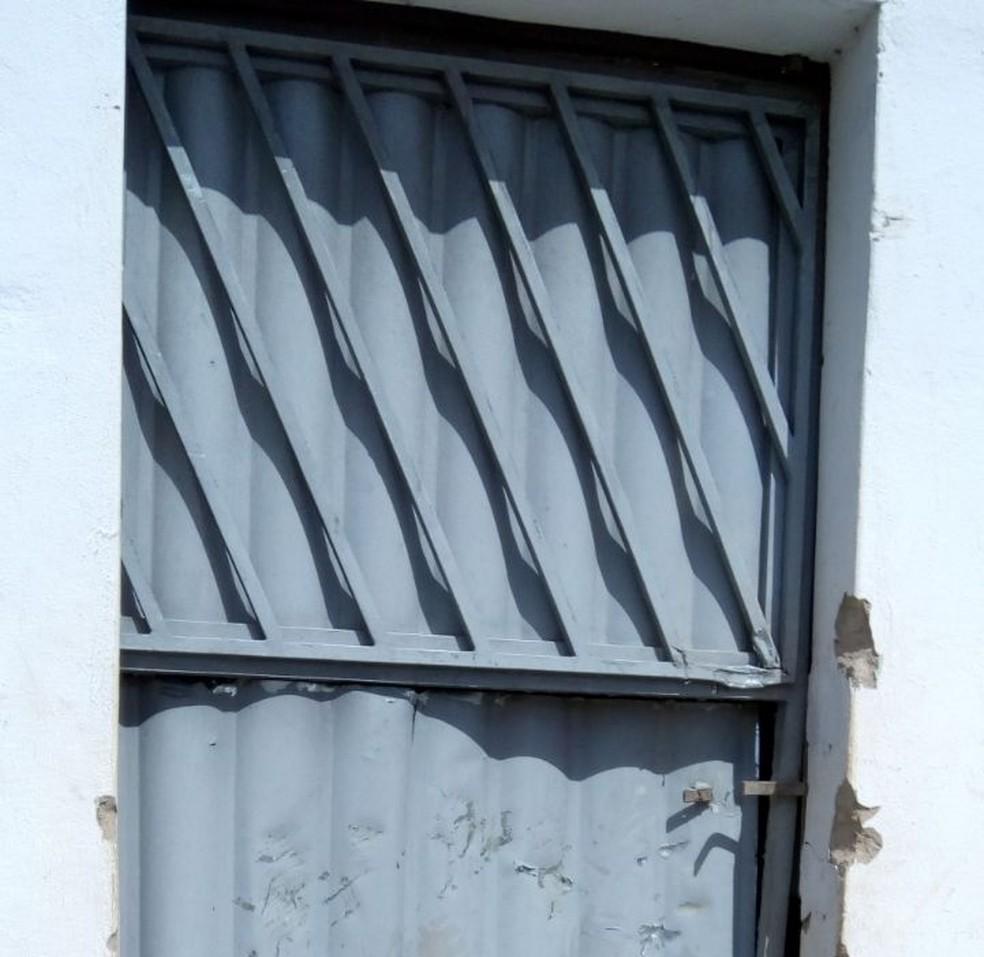 Porta da residência onde moravam as vítimas foi arrombada pelos criminosos (Foto: Robson Oliveira/Inter TV Cabugi)