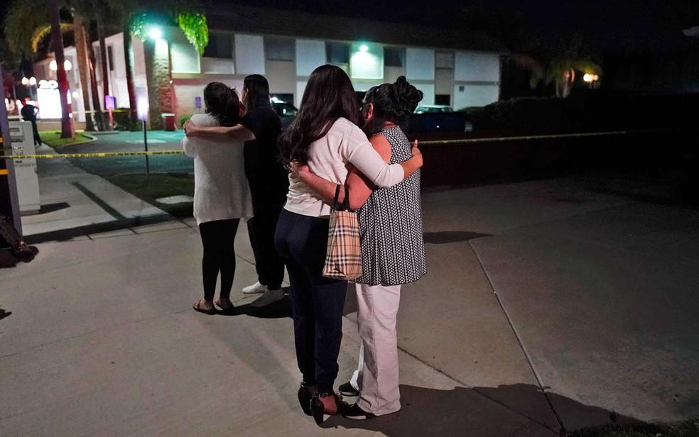Pessoas se consolam no local dos disparos em Orange — Foto: Jae C. Hong/AP