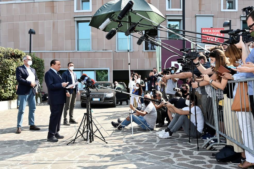 O ex-primeiro-ministro italiano Silvio Berlusconi fala com a imprensa nesta segunda-feira (14) ao deixar o hospital San Raffaele, em Milão, onde estava sendo tratado após testar positivo para Covid-19  — Foto: Flavio Lo Scalzo/Reuters