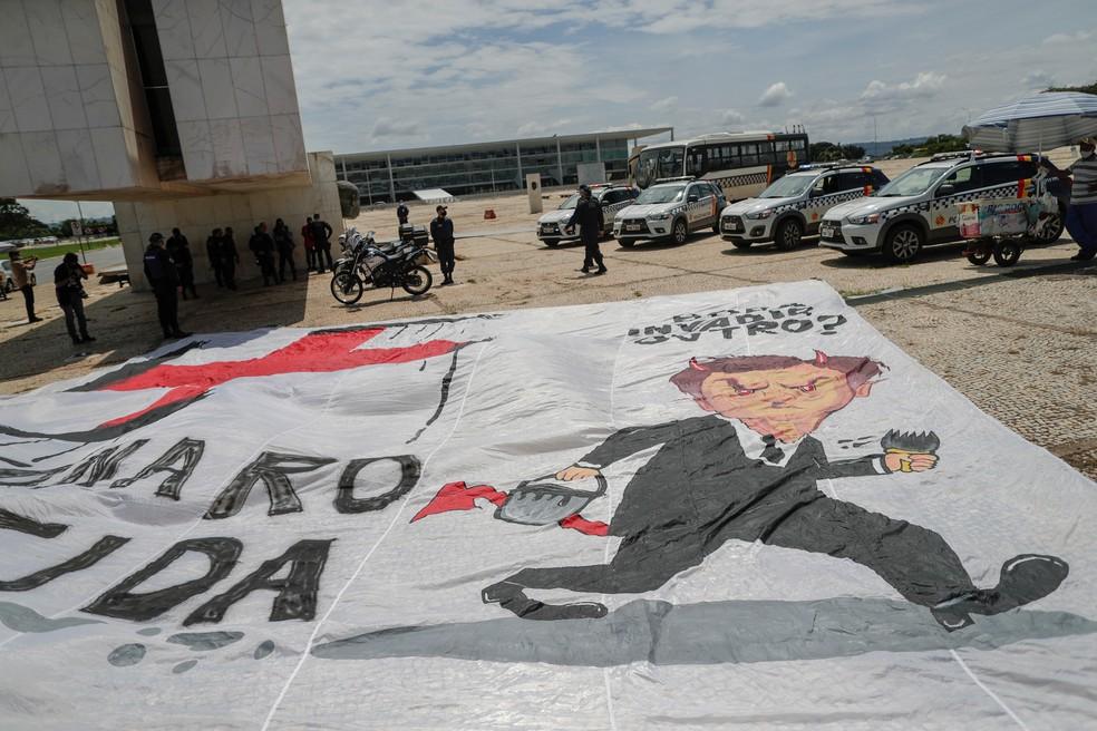 Grupo estende faixa contra presidente Jair Bolsonaro na Praça dos Três Poderes, em Brasília, nesta quinta-feira (18). — Foto: REUTERS/Ueslei Marcelino