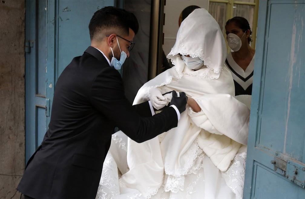 20 de março - Noivos palestinos usam máscaras e luvas durante a cerimônia de casamento no campo de refugiados de Deheisheh, perto da cidade de Belém, na Cisjordânia. Devido às medidas de prevenção contra o coronavírus, a festa contou apenas com a família direta dos noivos — Foto: Musa Al Shaer/AFP