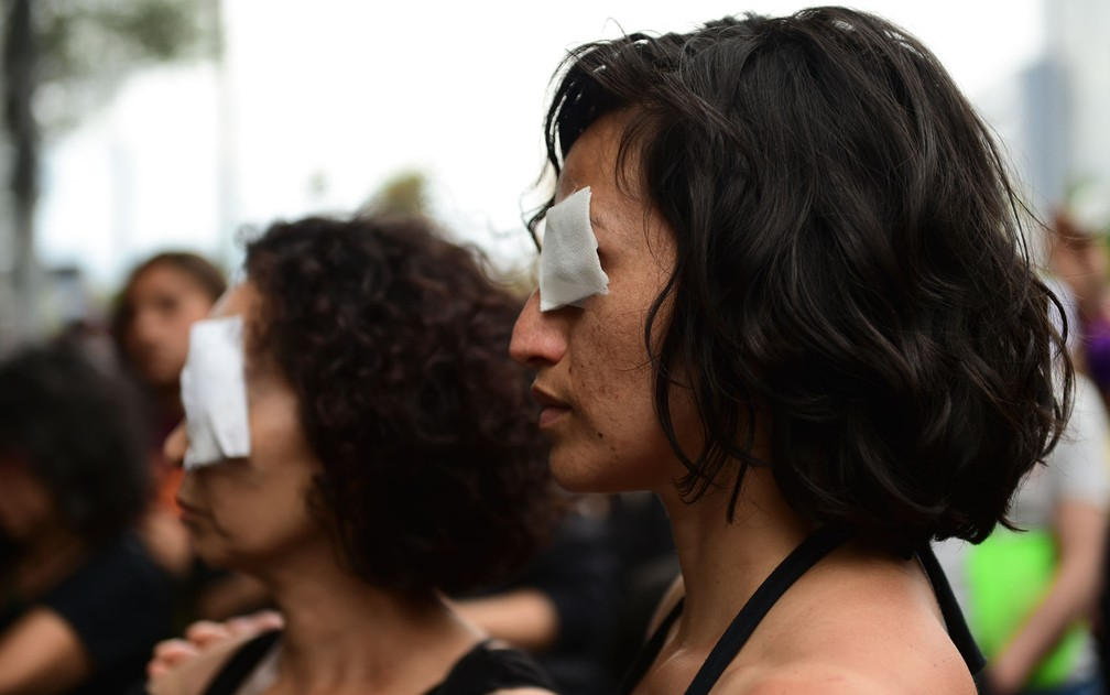 Mulheres vestidas de preto e usando curativos nos olhos participam de protesto em solidariedade aos manifestantes que sofreram ferimentos nos olhos, em Santiago, no Chile, na sexta-feira (1º) — Foto: Martin Bernetti/AFP