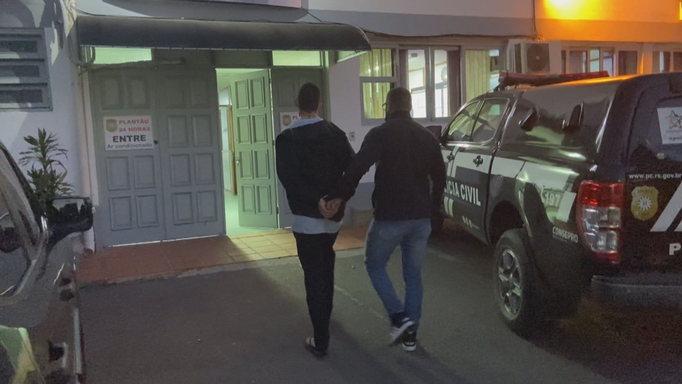 Suspeito é levado algemado para a Delegacia de Polícia, em Bento Gonçalves, no sábado (17). — Foto: Marcelo Dargelio/NB Notícias