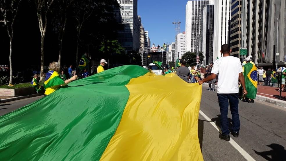 Bandeira verde amarela é estendida por manifestantes na Avenida Paulista — Foto: Vivian Reis/G1 SP