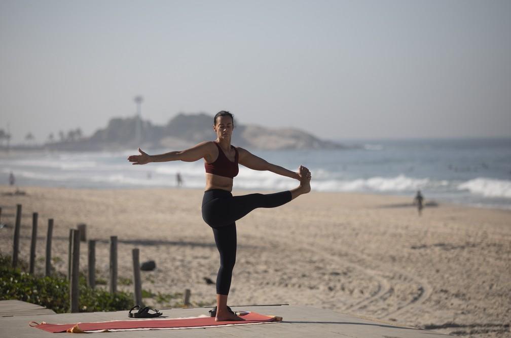 Mulher pratica ioga em Ipanema — Foto: AP Photo/Silvia Izquierdo