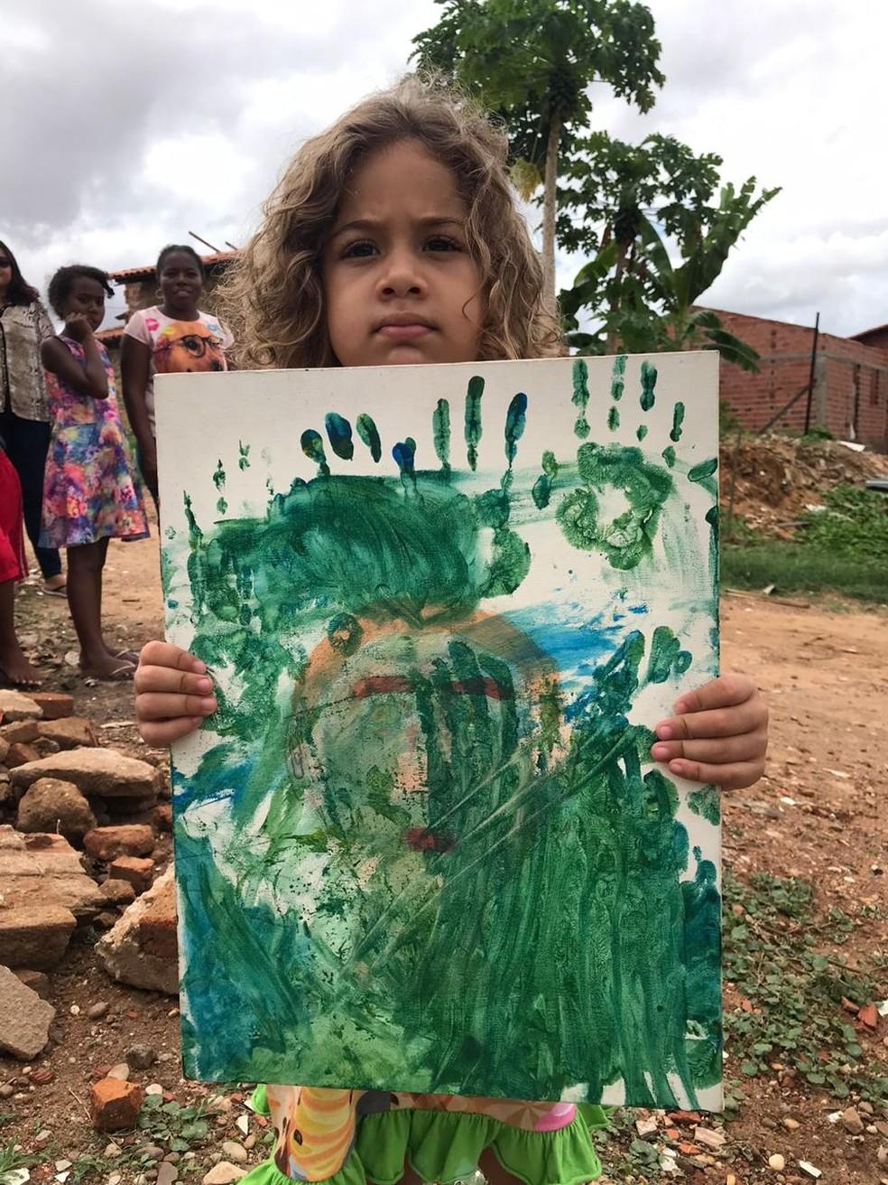 """Luna, 4 anos, mostra a """"obra de arte"""" que o irmão Isaac quer vender. — Foto: Neyara Pinheiro/TV Clube"""