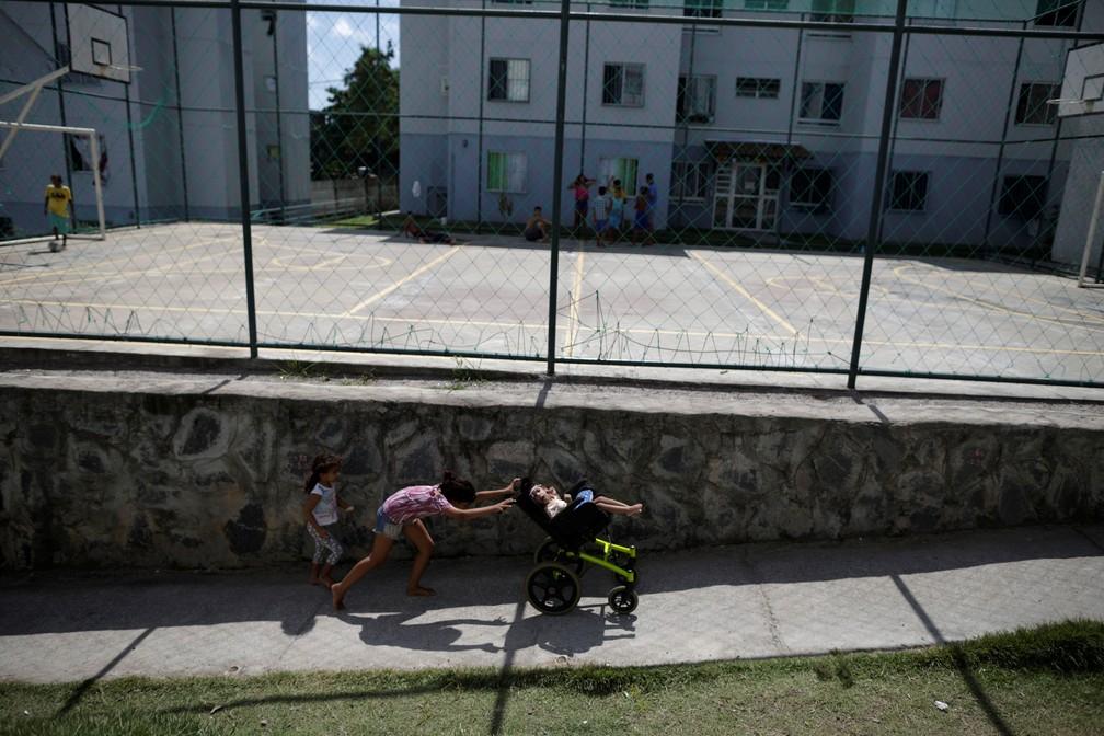 Luana Vieira, que tem dois anos e nasceu com microcefalia, é empurrada na cadeira de rodas pela irmã Vitoria Evillen, próximo a quadra do condomínio em que moram, em Olinda — Foto: Ueslei Marcelino/Reuters