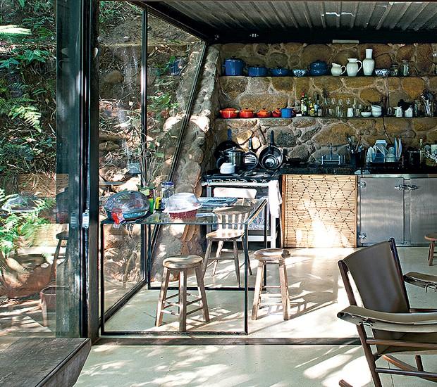 A cozinha é colada no muro de arrimo escalonado de pedras que acaba formando prateleiras para guardar as louças. Assim, armários não são necessários. Encaixados na base estão a bancada de granito com a pia, o fogão e o refrigerador horizontal (Foto: Leonardo Finotti/Casa e Jardim)