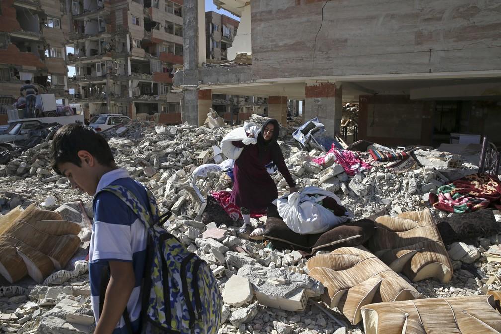 -  Sobrevivente do tremor carrega pertences para fora de prédios danificados em Sarpol-e Zahab, no Irã  Foto: Vahid Salemi/AP