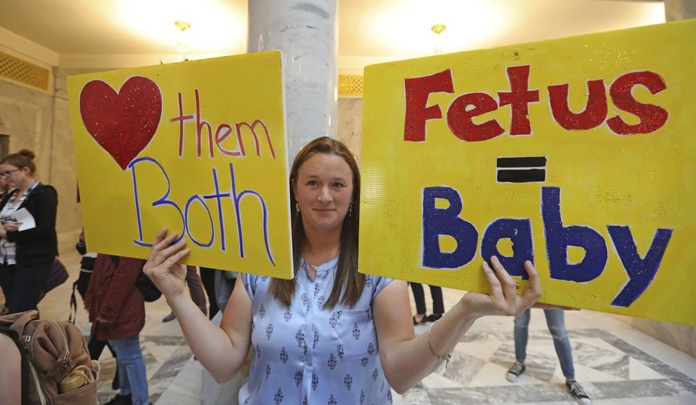 """Deanna Holland, vice-presidente da ProLife Utah, segura cartazes que dizem """"amem os dois"""" e """"feto = bebê"""" em um ato em Salt Lake City nesta terça-feira (21). — Foto: Rick Bowmer/AP"""