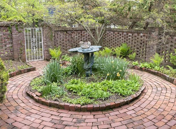 Vários jardins cercam a mansão. Na foto, uma fonte é cercada por tijolos e plantas (Foto: Ellis Sotheby's International Realty/ Reprodução)