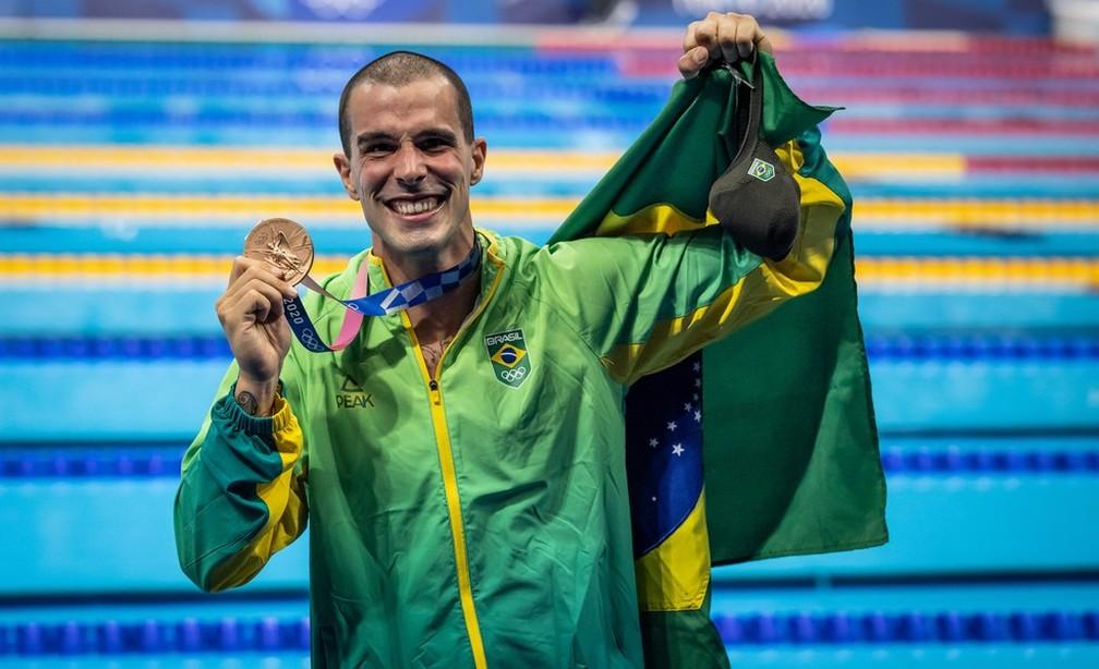 Bruno Fratus com a medalha de bronze dos 50m livre da natação nas Olimpíadas de Tóquio e a bandeira do Brasil — Foto: Jonne Roriz/COB