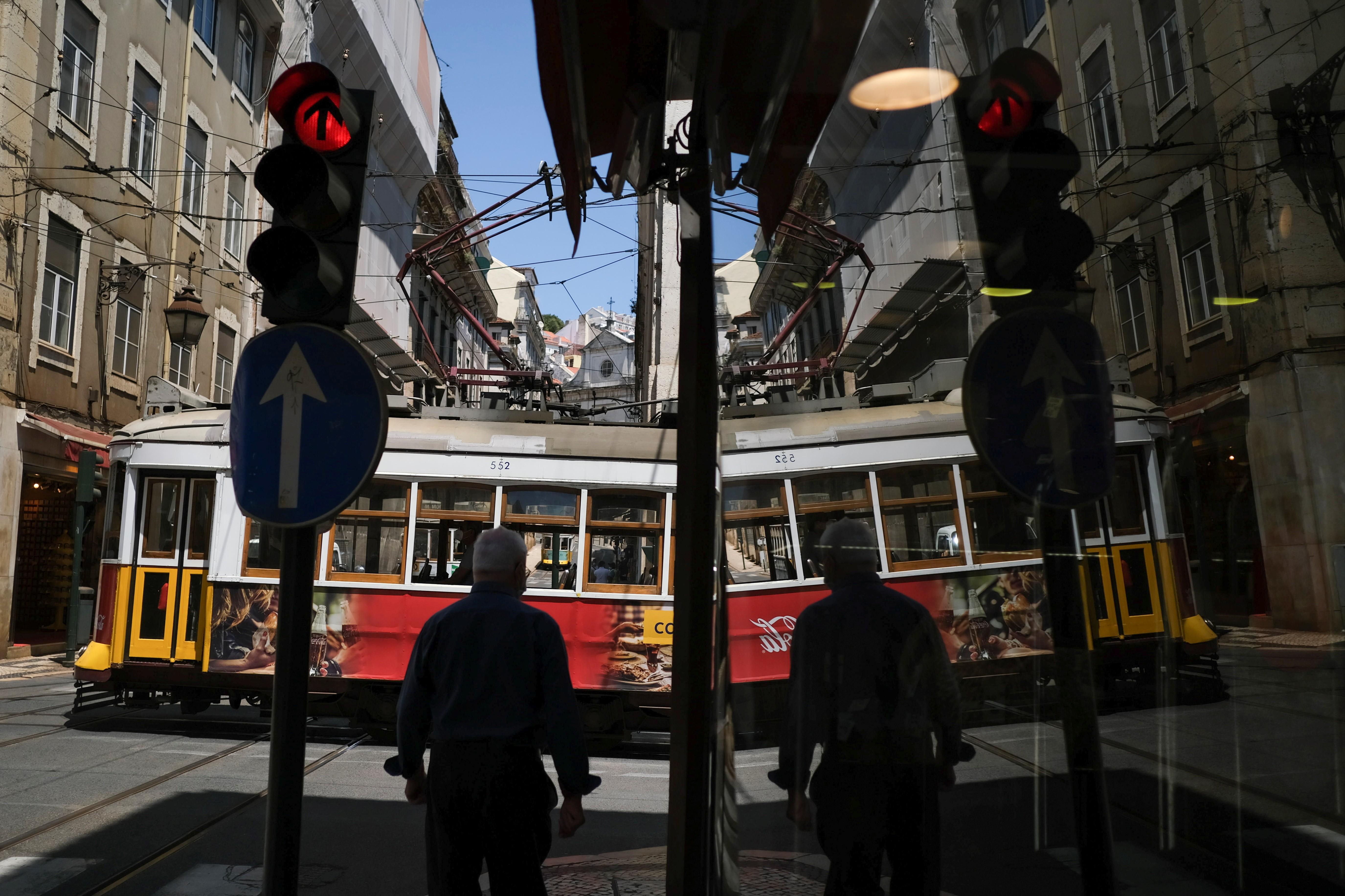 Homem diante de bondinho em uma rua de Lisboa