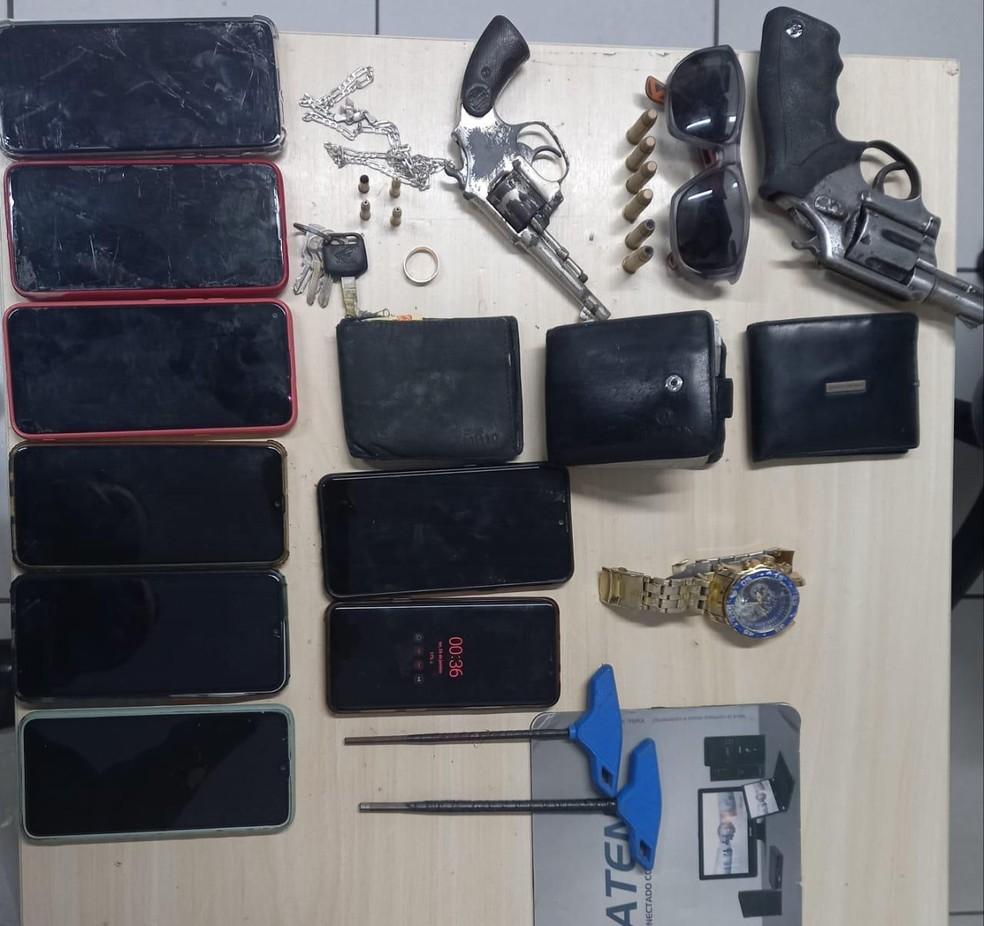 Duas armas, celulares e outros objetos roubados durante assalto foram apreendidos após perseguição a dupla de assaltantes. Um dos suspeitos morreu. — Foto: Divulgação/PM