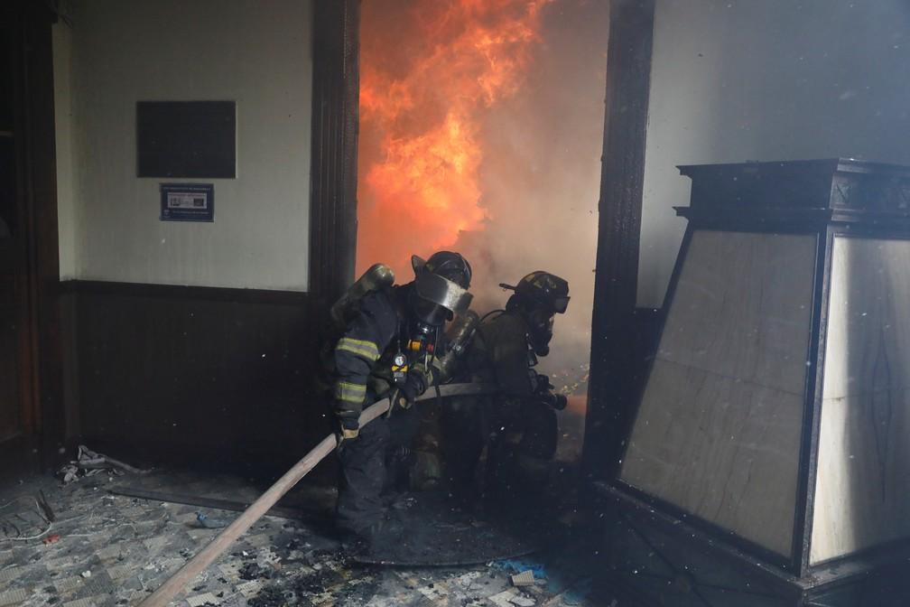 Bombeiros tentam apagar incêndio após manifestantes atearem fogo no Congresso da Guatemala neste sábado (21) — Foto: Luis Echeverria/Reuters