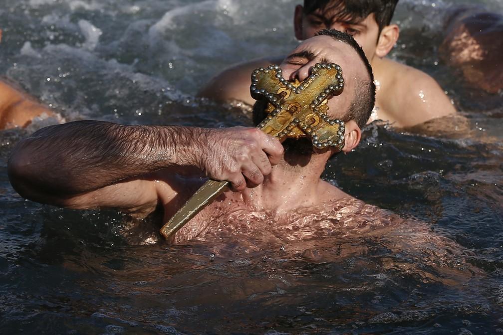 7 de janeiro - Nicolaos Solis beija a cruz de madeira que foi lançada nas águas pelo patriarca ecumênico Bartolomeu I, durante a cerimônia da Epifania para abençoar as águas no Golden Horn, em Istambul, na Turquia (Foto: Emrah Gurel/AP)