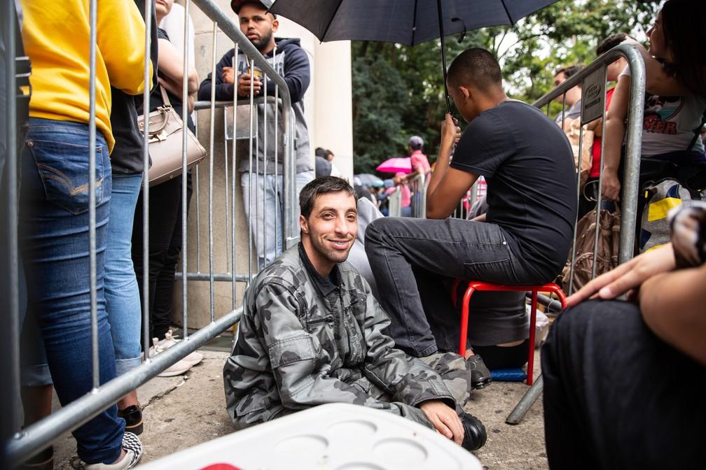 Sentado no chão, fã aguarda na fila diante do Estádio do Pacaembu para comprar ingressos do show de 30 anos de carreira da dupla Sandy e Junior. Mesmo sem chuva, guarda-chuvas eram usados para proteger contra o cocô dos pombos pousados na fachada do estádio — Foto: Fábio Tito/G1