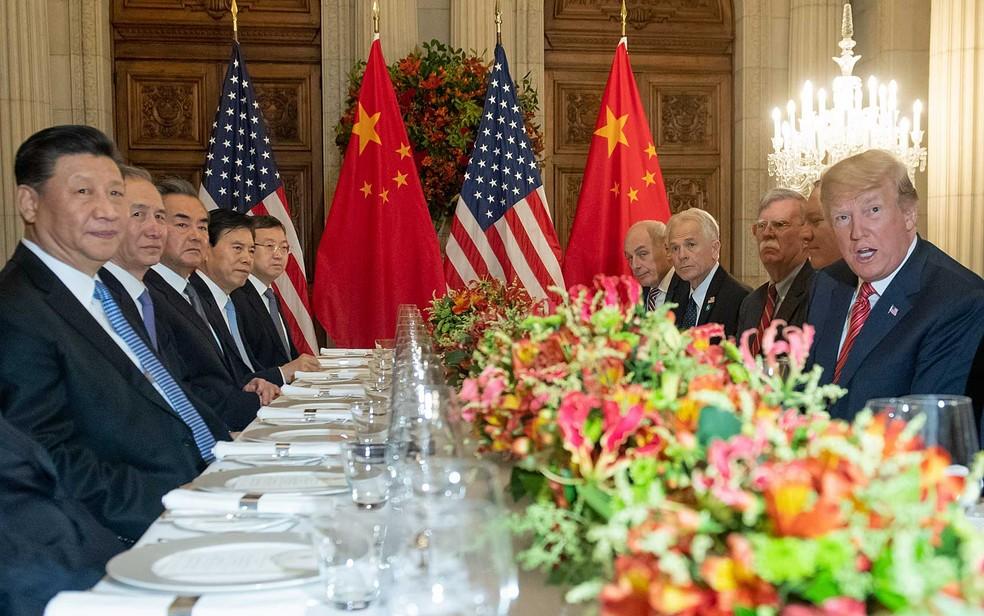 O presidente dos EUA, Donald Trump (à direita na mesa), e o presidente da China, Xi Jinping, juntamente com as delegações dos dois países, durante jantar após a cúpula do G20 em Buenos Aires — Foto: Saul Loeb / AFP Photo